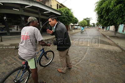 Dancing with the Devil production stills. Pastor Dione stops to talk with a local in Vila Aliana, Rio de Janeiro. (Australfoto/Douglas Engle)
