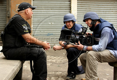 Dancing with the Devil production stills. DOP Lance Gewer, right, Jon Blair and Policeman Jacyr during police raid in Complexo do Alemao (German Complex). (Australfoto/Douglas Engle)