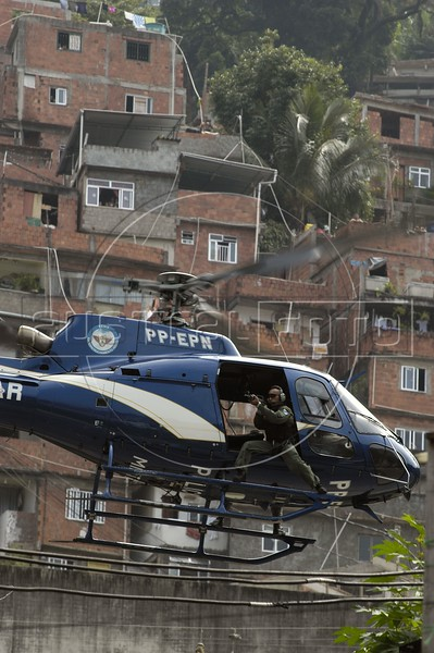 A police helicopter flies over the Rocinha slum in Rio de Janeiro, Brazil, Monday, April 12, 2004. According to reports, about 1000 police officers invaded the slum after a battle between rival drug traffickers erupted during the weekend. At least eight people died during the confrontations. Gun battles between rival drug gangs, and police are common.  Many slums in Rio de Janeiro have long been run by drug barons, often with links to local politicians and police. The levels of violence are comparable to a war zone, and recently the Deputy Mayor of Rio, Luiz Paulo Conde, proposed an Israeli-style wall around the slums as a solution.