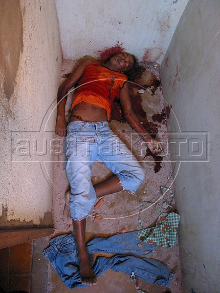 A shootout victim lies in a pool of blood in the Roquete Pinto favela, or slum, in Rio de Janeiro, Brazil, where Police Inspector Roberto Ubiratan Dias, 29, was killed by gang members as he was conducting an investigation. The assailants threw a grenade from the second story of a house at the inspector and police officers who accompanied him. A firefight followed in which the inspector and two assailants were killed. Shootouts between rival drug gangs and the police are common in Rio and the death toll rivals that of declared war zones.(AustralFoto/Douglas Engle)