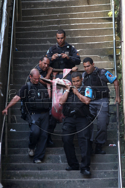 Rio de janeiro State Police Police (PMERJ) carry a body down a stairway from a slum where a shootout took place about 1 hour earlier in Rio de Janeiro, Brazil, Oct. 21, 2009. (Douglas Engle/Australfoto)