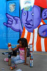 A baby plays while Brazilian popular artists paint a train at Engenho de Dentro station, Rio de Janeiro, Brazil, Nov. 3, 2007.<br /> More than 20 street artists participated in the event, sponsored the Supervia commuter railroad and by non-governmental organizations that work with social assistance for youths from slums and poor communities.  (AUSTRAL FOTO/RENZO GOSTOLI)