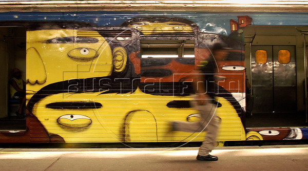 A man runs to take a train, painted by popular artists at Central do Brasil (Brazil's Central station), Rio de Janeiro, Brazil,  Feb. 7, 2006. Popular artists Otavio and Augusto Pandolfo, knows as Os Gemeos (The Twins), Nina, Ise and Coio have paints a train with four wagons of 90 meters, inaugurated today. The work is patrocinated by Supervia , a brazilian railways company in a program to paints buildings and other trains by artists.. (FOTO:AUSTRAL FOTO/RENZO GOSTOLI)