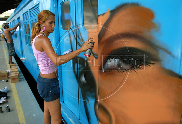 Brazilian popular artist Panmela Castro, 26, paints a train at Engenho de Dentro station, Rio de Janeiro, Brazil, Nov. 3, 2007.<br /> More than 20 street artists participated in the event, sponsored the Supervia commuter railroad and by non-governmental organizations that work with social assistance for youths from slums and poor communities.  (AUSTRAL FOTO/RENZO GOSTOLI)