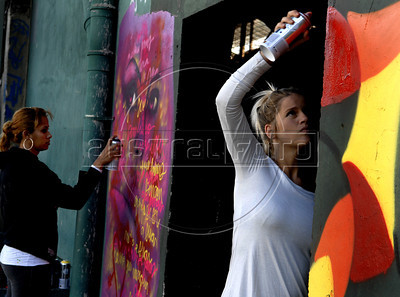Artist Panmela Castro, left, and a colleague paint on the wall of Fundicao Progresso, Rio de Janeiro, Brazil, August 5, 2011. (Austral Foto/Renzo Gostoli)