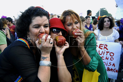 "Women bite the""sin apple"" during the ""Marcha das vadias"", inspirated by the Slut Walk, a march against sexism and in favor of women's rights wich started in Canada and has been spreading all around the world, at the Copacabana beach, Rio de Janeiro, Brazil, July 2, 2011. Women at the ""Marcha das vadias"" in Rio complain about the high rates of violence against women in Brazil. (Austral Foto/Renzo Gostoli)"