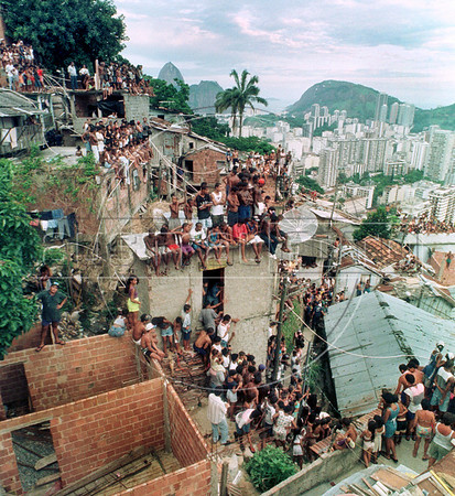 """Neighbourhood assist the pop star Michael Jackson singing and dancing on the roof of a building in the Dona Marta slum, Rio de Janeiro, Brazil, Feb. 11, 1996 during the filming of the video for his song """"They Don't Care About Us.""""  (Austral Foto/Renzo Gostoli)"""