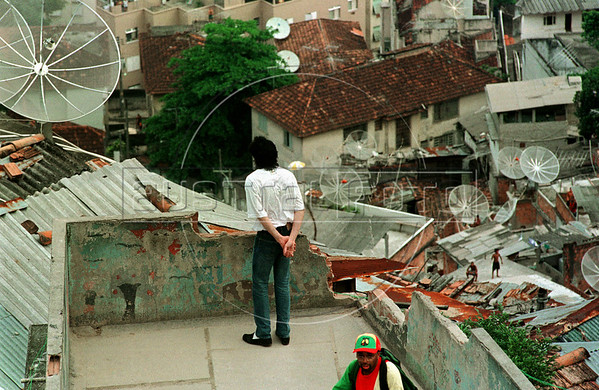 "Pop star Michael Jackson performs on the roof of a building in the Dona Marta slum, Rio de Janeiro, Brazil, Feb. 11, 1996 during the filming of the video for his song ""They Don't Care About Us.""  (Austral Foto/Renzo Gostoli)"