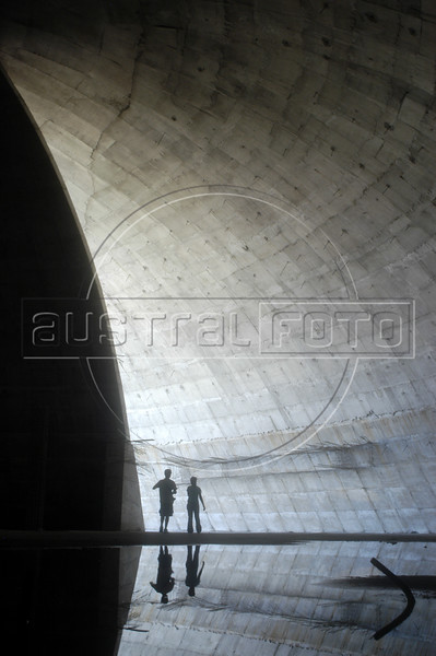 Visitors walk through an unfinished building designed by Brazilian architect Oscar Niemeyer in Niteroi, a neighboring city of Rio de Janeiro, Brazil. Niemeyer is known for his futuristic round and curving designs, and in particular for designing most of the buildings in Brasilia, the planned Brazilian capital. Born in Rio de Janeiro in 1907, Niemeyer's formative experience was in 1934 when he joined a team of Brazilian architects collaborating with French architect Le Corbusier on a new Ministry of Education and Health in Rio de Janeiro. It was while working on this project that he met the mayor of Brazil's wealthy central state, Juscelino Kubitschek, who would later become President of Brazil. As President, he appointed Niemeyer to be the chief architect of Brasilia, a project which occupied all of his time for many years. (AustralFoto/Douglas Engle)