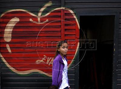 A girl pasts in front of a wall painted by graffiti artist Panmela Castro in Rio's Gamboa district as part of Arte Rua (street art), International Contemporary Art Fair of Rio de Janeiro, Rio de Janeiro, Brazil, September 10, 2011. (Austral Foto/Renzo Gostoli)