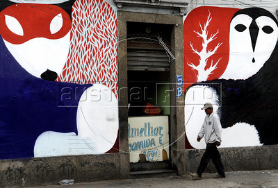 A man pasts in front of a wall painted by graffiti artists in Rio's Gamboa district as part of Arte Rua (street art), International Contemporary Art Fair of Rio de Janeiro, Rio de Janeiro, Brazil, September 10, 2011. (Austral Foto/Renzo Gostoli)