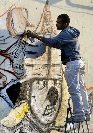 A graffiti artist paints on the wall of a house in Rio's Gamboa district as part of ArtRio, International Contemporary Art Fair of Rio de Janeiro, Rio de Janeiro, Brazil, September 7, 2011. (Austral Foto/Renzo Gostoli)