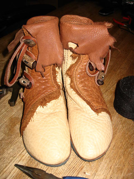 My nephew Ryan's new boots!  Sand three button moccasins, with tobacco buffalo natural edge trim, burnt cork deerskin natural edge flap, and antler barrel buttons.  Ryan's moccasins are soled in leather so that they are authentic to what the Mountain Men would have worn.  What fun to have helpers in the shop!