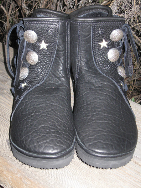 A new pair of three button moccs for a special moccasin lover!  These are made from black buffalo hide, with black button trim in the slight curve design.  The cutout stars are backed with her very own gold deerskin.  The finishing touches are a black deerskin top welt, and silver dragon buttons.  Nice!