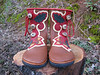 Terrestrial boots for an action girl!  Sometimes it takes a bit for the inspiration to come.. but when it does!  I love it!  This pair of three button tobacco moccasins, has a red bullhide button trim, cut to accent the oak leaves and acorns that are appliqued in deerskin.  Embroidery is added to connect the appliques, and then a palomino deerskin underlay accents it all.  Antler crown buttons and a red deerskin top welt finish them off.  Be sure to check out the heels on this pair - next photo - it's fun to be creative!