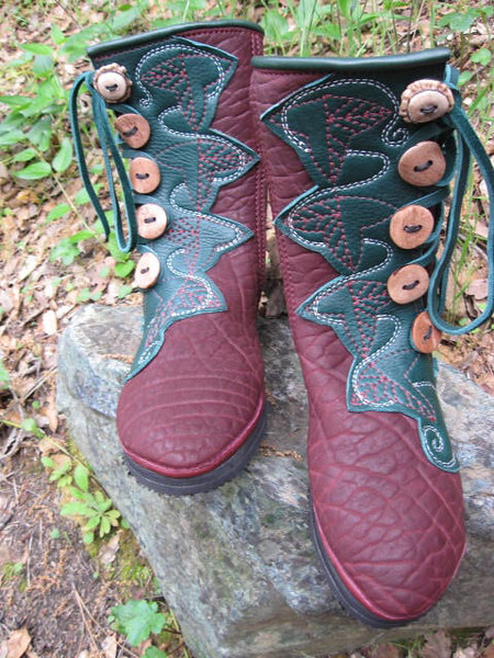 It's fun for me when the person designing the boots makes a drawing of what they would like on their new boots!  This button trim represents the leaves used to wrap food in the Tolkien stories.  These 5 button moccasins are made from redwood buffalo hide, with forest green button trim.  I used redwood and white thread to do the ornamental embroidery.  The top welt is forest green deerskin, and they are finished off with one antler crown at the top of each boot, and antler sidecut buttons going down.  The soling is thin cushi with Spikeless Golf Vibram soles.  These boots will be a nice accompaniement for some amazing musicians!