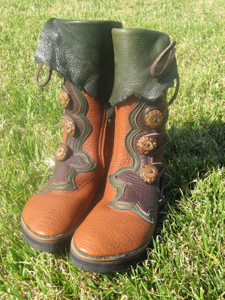 Meghan's boots get the award for the most traveling before they ever get on her beautiful feet!<br /> Five Button Tobacco Buffalo, Chocolate Flower Button Trim, Forest Green Deerskin Underlay, Natural Edge Flap, Medium Antler Crowns, Thin Cushi, Spikeless Golf Vibram Soling.