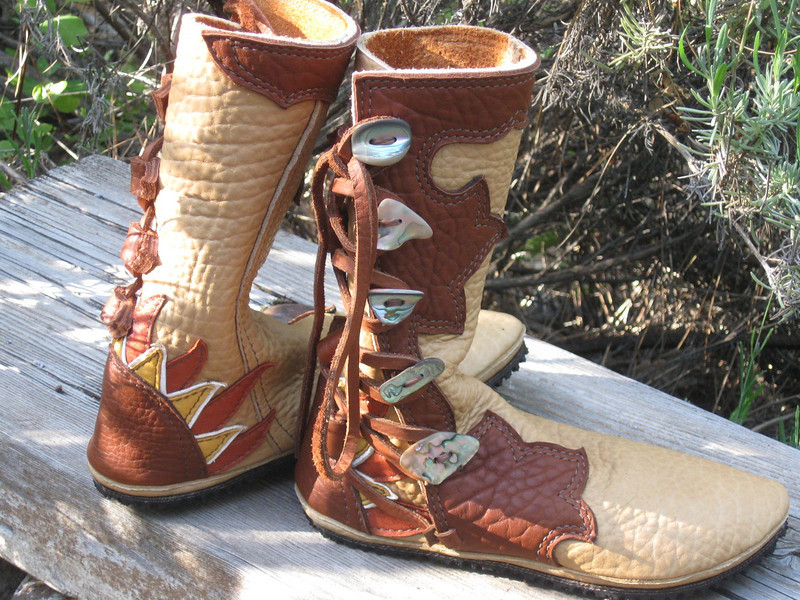 Sand Buffalo is occasionally available - and it is so nice!  It has deep grain and some color varigation.  This pair of five buttons moccs is sand buffalo for the main part of the boots, with tobacco 'extreme flower' design going around the leg.  The heel includes an underlay of a sun in rust, gold, and white deerskin.  Abalone buttons and conveyor belt soling finish off these beauties.