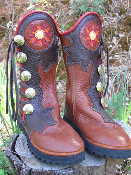 """Beautiful boots are designed in many places, especially EarthDance.   <a href=""""http://www.earthdancelive.com"""">http://www.earthdancelive.com</a><br /> Bess designed her boots there this last year.  The energy that is exchanged when 1,000's of people are praying for peace TOGETHER, is tangible.  There are many ways to pray, and a good portion of them are conducted at EarthDance.<br /> Five Button Tobacco Bullhide, Chocolate Extreme Flower Button Trim, Cutout/Applique Sun, Pointy Rays Orange Goatskin, Curvy Rays Red Deerskin, Center Gold Deerskin, Full Welt Red Deerskin, Brass QuickSilver Buttons, Thin Cushi, Full Lug Vibram Soling."""