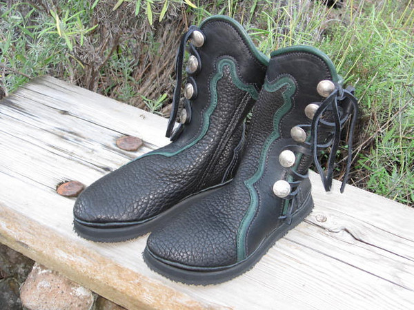 Five button boots, black buffalo, with black bullhide button trim in the points and curves design going around the inside of the leg.  Green deerskin underlay and green deerskin full welt.  Buffalo and Indian Head coin buttons.  Thick cushi midsole and spikeless golf vibram soling.