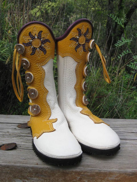 And around the world we go!  White buffalo boots, with gold button trim in the flower design, going around the inside of the leg.  Full welt edging in eggplant deerskin, with a combination cutout and applique of a sun in white, eggplant and gold.  Antler sidecut buttons, spikeless golf Vibram soling.