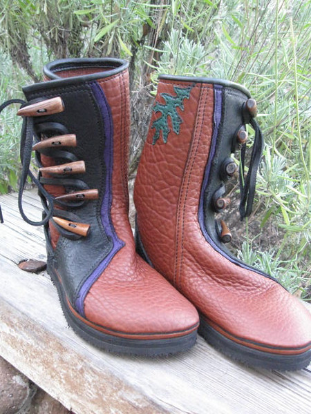 Five button tobacco buffalo hide moccasins, black natural edge button trim, with a purple deerskin natural edge underlay, black top welt, green leaf applique on inside of leg, antler point buttons, thick cushi, spikeless golf Vibram soling.