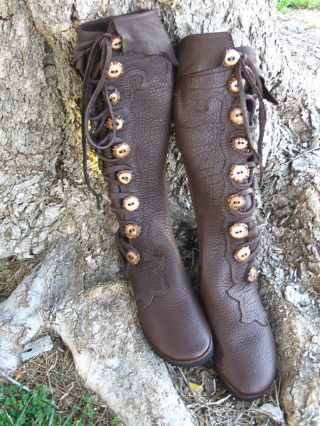 Princess Tuesday's beautiful boots are made from chocolate buffalo hide.  The extreme flower design goes up and around the leg, with a small natural edge deerskin flap adorning the top of the boot.  There is an olive cowhide triskellion appliqued to the heel, to identify her clan.  She chose medium dye antler crown buttons, and finished them off with the Newflex Vibram soling.  Many days of happy strolling with comfortable feet - as it should be for a fairy princess as beautiful as Tuesday... Blessed Be.