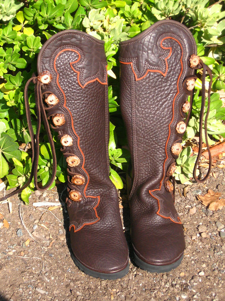 """7 button moccasins, chocolate bullhide, with chocolate button trim in the 'extreme flower' design going around the leg, going up the leg in points and curves, with an 1/8"""" underlay of burnt cork deerskin, full welt in chocolate deerskin, and antler crown buttons."""