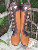 Nine Button Moccasin, Tobacco Buffalo Hide, Chocolate Lotus Flower Button Trim, going up leg in Points and Curves, and going around the leg, Redwood Deerskin Underlay, Redwood Deerskin Full Welt, Sun Cutout/Appliques, Medium Dye Antler Crown Buttons.