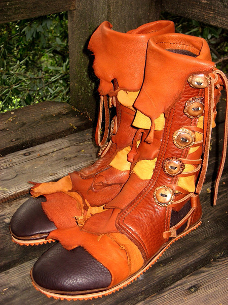 This type of applique is called a 'full rag'.  It involves layering of deerskin natural edge pieces over almost the entire boot.  This pair of five button moccasins is made from chocolate, with various shades of burnt cork and dusk deerskin, a natural edge button bullhide button trim, and a top flap of burnt cork deerskin.  The buttons are antler crowns in the medium dye.  Fun!