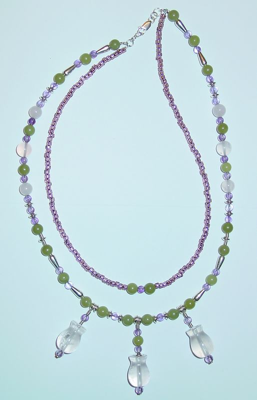 Jeanne Kramer-Smyth<br> Entry for Category 4: Gemstone Beads<br> List of FireMountainGems Products:<br> 513330CL: Madagascar rose quartz (N), grade A, vase 17x12 to 15x10mmm<br> WE3716GS: Bead, peridot serpentine 'jade' (N), round, 6mm, sold per 16-inch strand. <br> WE4039GS: Bead, rose quartz (N), round, 8mm, sold per 16-inch strand.<br> WE4040GS: Bead, rose quartz (N), round, 10mm, sold per 16-inch strand.<br> 503481GS: Bead, amethyst (N), round, 4mm, C grade, sold per 16-inch strand.<br> WE1765MB: Bead, sterling silver, smooth teardrop, 8x4mm, sold per package of 20.<br> WE1759MB: Bead, sterling silver, coil, 3x2mm, sold per package of 50.<br> WE1691MB: Bead, sterling silver, smooth saucer, 4mm, sold per package of 50.<br> 654960SB: SEEDBEAD #8 RD HL SIL LN LILAC 35GM<br> 658440FN: HEADPIN SS 2 INCH 26GA(.016) PK10 <br> 632025FN: Sterling silver lobster claw clasp with ring, medium, sold per package of 5.<br> 652185FN: Sterling silver crimp tube, smooth outside, 2x2mm, sold per package of 100.<br> 654462FN: Sterling silver jumpring, pre-soldered, approximately 22 gauge, round, 4mm, sold per package of 100.<br> 652346FN: 4.5mm, sterling silver, sold per package of 10.