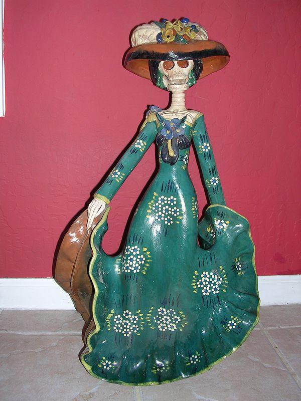 "Clay female figure commonly called a ""catrina."" Represents the high society women during the turn of the 19th century and first two decades of the 20th century as depicted by famous Mexican artist Jose Guadalupe Posada.  This catrina was made  by an unknown artisan."