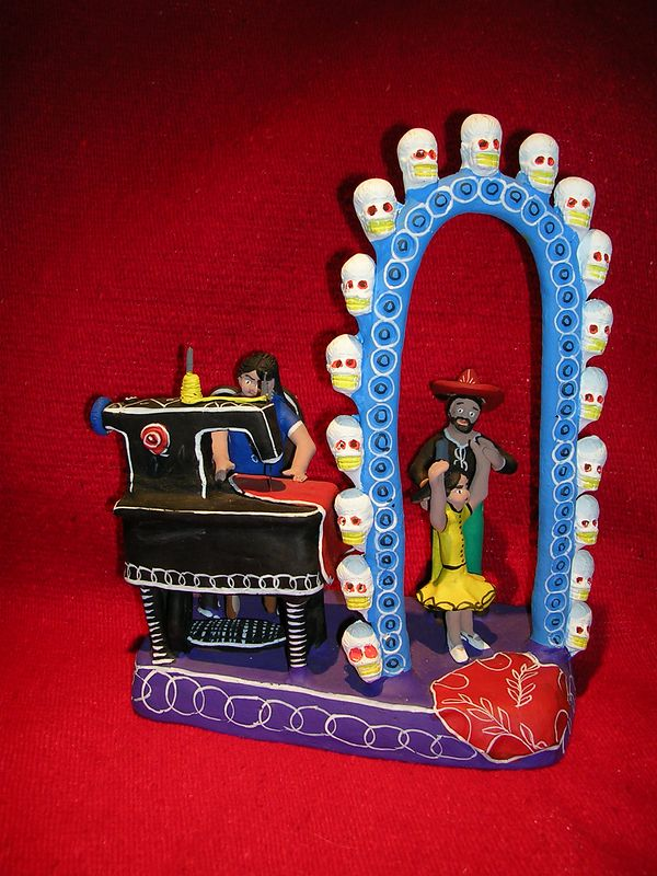 Handmade clay scene of a seamstress sewing on her machine while the father measures his daughterl in a doorway surrounded by white skulls.  Unknown artisan from Ocumicho, Mexico.  The skulls may have been included to indicate this family is making preparations for Day of the Dead or simply because objects with any conenction to Day of the Dead sell faster.
