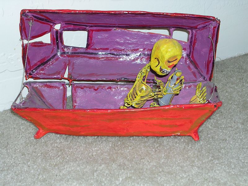 Paper mache figure of a skeleton in a coffin by Saulo Moreno.