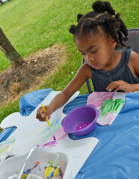 "Amelia Dyer, 3, of Fitchburg, works on the unify Fitchburg art puzzle project at the ""Juneneenth Celebration"" at Riverfront Park in Fitchburg on Saturday afternoon. SENTINEL & ENTERPRISE / Ashley Green"