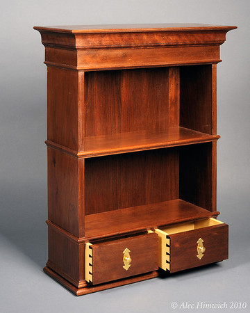 "This classically proportioned wallhung cabinet is made primarily of Peruvian walnut and secondarily poplar.  The finish is shellac and wax.  <br /> <br /> The length and width of the cabinet follow the ""golden rectangle"".  The vertical proportions are after the Doric Order seen in classical architecture.  The shelves comprise the pedestal; the shelves, the column; and the crown, the architrave.<br /> <br /> The back is tongue and grooved.  As with the other wallhung cabinets shown here, this cabinet is designed to be hung from the wall with a French cleat."