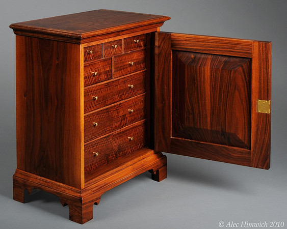 This spice chest is of a representative style of spice chests common among the Quakers of Chester County. These chests were popular in the 18th century as a means of secure storage for valuable spices.<br /> <br /> The primary wood is black walnut. The drawer fronts are 4 way bookmatched quilted claro walnut. The door front is bookmatched walnut burl. The secondary wood is poplar.<br /> <br /> Joinery is both through and half blind dovetails. The metal fittings are a mortise keyed lock and brass drawer pulls.