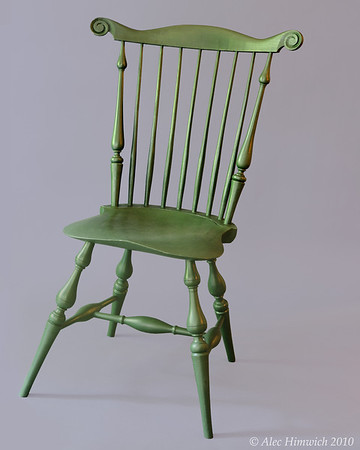 Popular during the 18th and 19th centuries, Windsor chairs have seen a resurgence in interest. <br /> <br /> The unique feature of this fanback Windsor chair is the carved whorls in the crest rail.  Several woods are used: pine for the seat, red oak for the spindles and crest rail, and maple for the spindle posts and baluster turnings.  The finish is milk paint (Lexington Green) and tung oil.