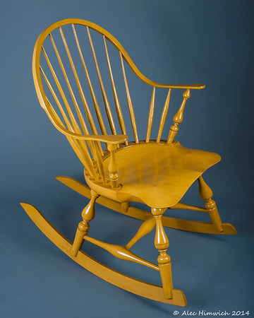 The unique feature of this continuous arm Windsor rocking chair is the double curved arm which constitutes the back and the arms of the chair and rockers. <br /> <br /> Several woods are used: pine for the seat, red oak for the spindles and rockers, white oak for the continuous arm, and maple for the arm posts and baluster leg turnings.  The finish is milk paint (Mustard yellow), tung oil, and shellac.