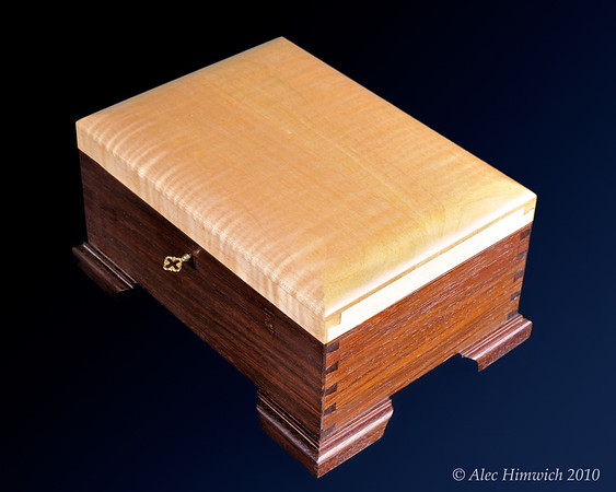 This jewelry box shows half blind dovetails and hand cut molded feet with mortised keyed lock.  The box is lined with Chinese brocade fabric and a glass mirror.  THe woods used are Peruvian walnut and quilted maple with a shellac finish.