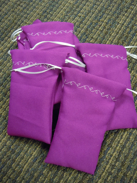 "A set of 12 Fuschia/purple/pink Drawstring bags. Double drawstring closure, satin ribbon. There is a white vine leaf design. 3 1/8"" x 6"". One set available, $5"