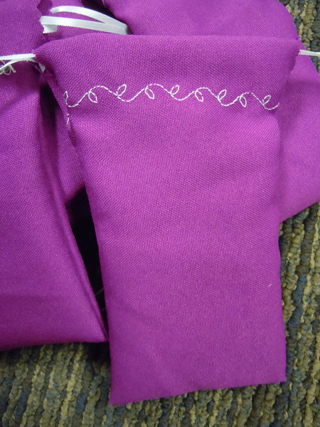 "A Close up of one bag<br /> A set of 12 Fuschia/purple/pink Drawstring bags. Double drawstring closure, satin ribbon. There is a white vine leaf design. 3 1/8"" x 6"". One set available, $5"