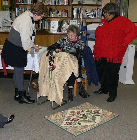 Mary giving rug hooking demonstration at local Rhea Library. The hanging at her feet is another of her creations.