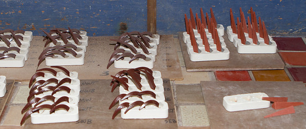 To tell if the firing is done correctly, special, calibrated clay wedges are put in the kiln.  Each of the three wedges droops at a different temperature/heat exposure.  Used on the left, unused on the right.
