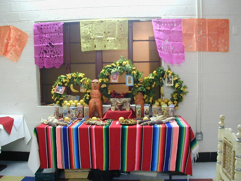"""2002- A Community ofrenda was erected and many added elements to the table such as incense burners with copal, candles, skeleton figures, fruits/nuts, marigolds, etc.  The tall figure just left of center is a """"pan de muerto"""" - a special bread baked for Day of the Dead and shaped into a man."""