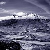 Mount St. Helens in Infrared.  The innocent cloud collar surrounds a very ominous, medieval look to this mountain's blast side covered with ash.