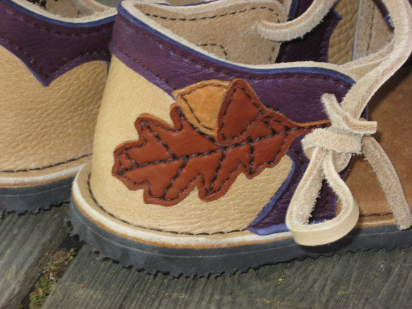 Oak Leaf and Acorn in Burnt Cork and Dusk Deerskin, on heel of a sandal made from Sand Bullhide, with Eggplant Purple Deerskin Trim.