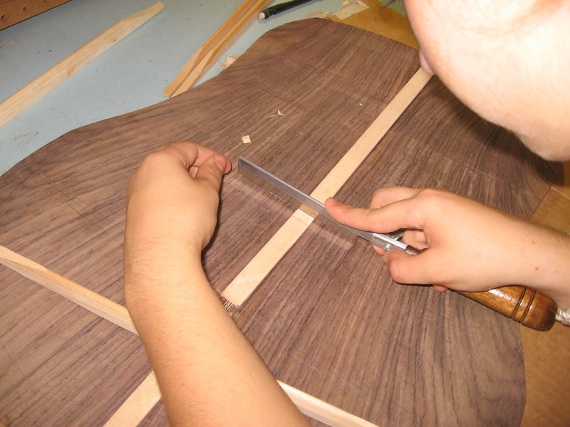 A center strip is glued across the joint on the inside of the guitar, and then slots are cut in it for the back braces.