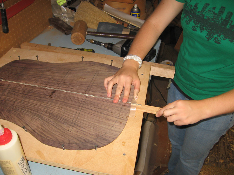 A stick raises the edge to be glued. When the stick is removed, downward pressure pushes the glue joint together.