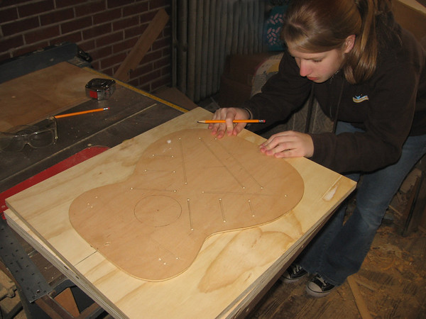 Lydia laying out the guitar pattern on the top of the guitar frame. She is making a plywood frame to hold an OM (Orchestra Model) or 000 guitar (H.S. senior project)